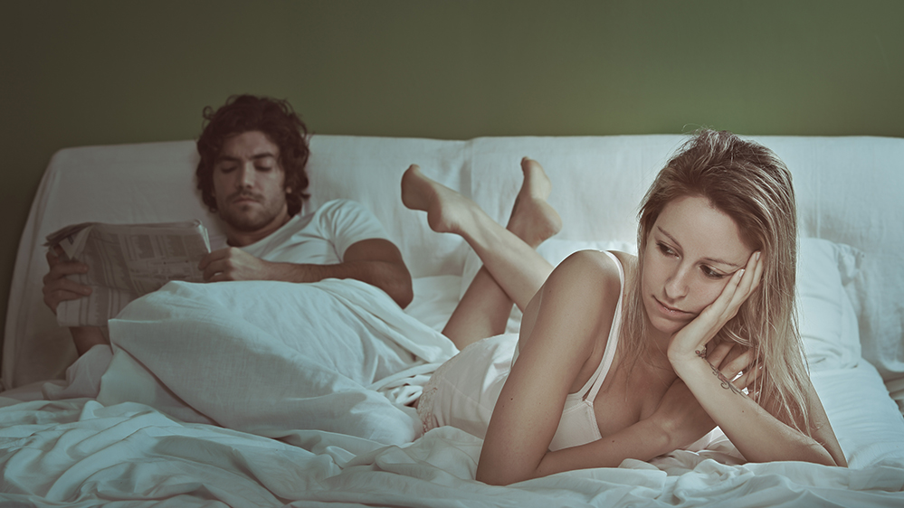 Woman in bed feels alone and sad