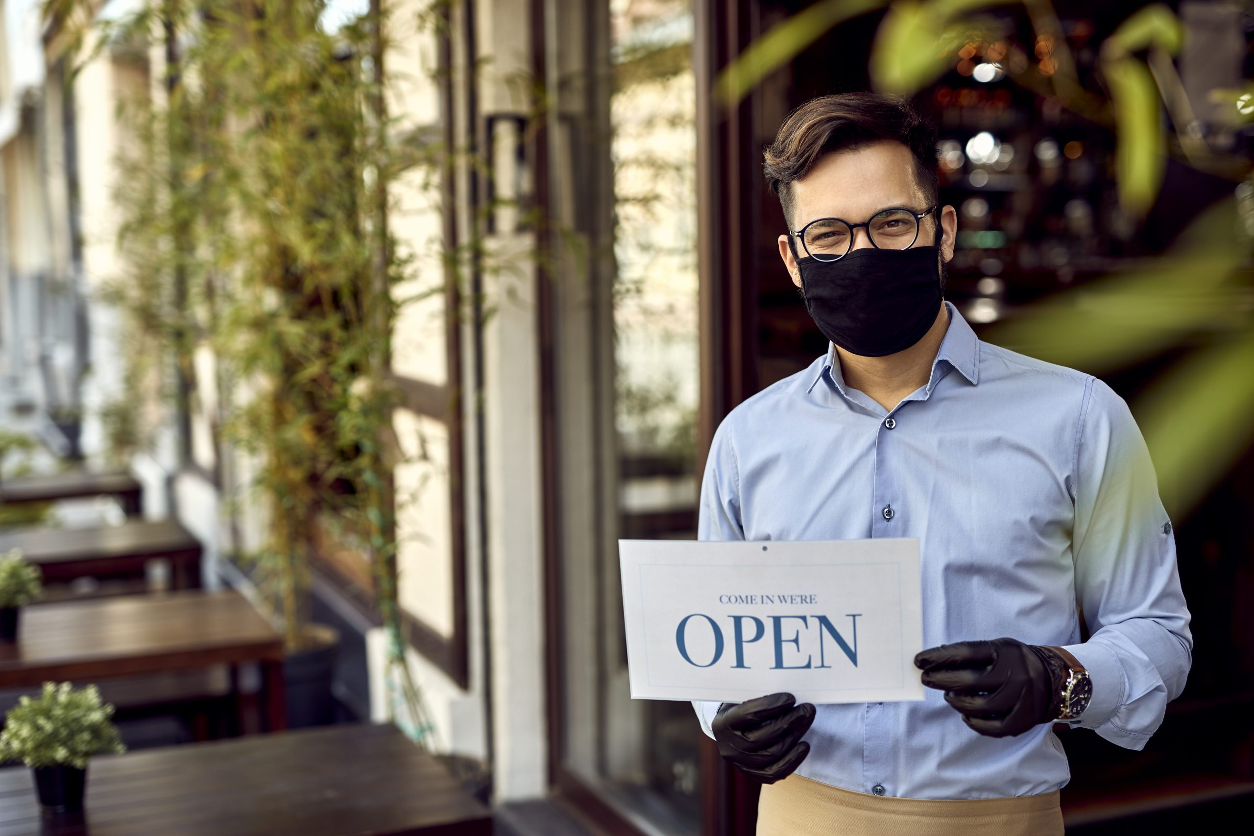 Happy cafe owner holding open sign while wearing protective face mask.